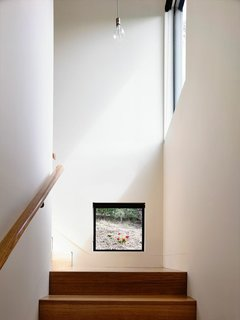 """""""I love this low-level stair window. It's at head height when you're at the bottom of the stairs; it gives you a glimpse of, and connection to, the garden outside. Most of the windows capture what I'd call 'hero shots,' but some, like this one, are completely unexpected."""""""