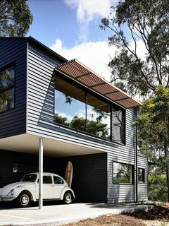 Timber battens were used on north-facing windows to prevent excessive heat in the summer. The exterior is clad in Scyon's Linea weatherboard and covered in Dylux's Western Myall paint. Beneath the upper floor, a little nook makes for the perfect covered carport and storage spot for surfboards.