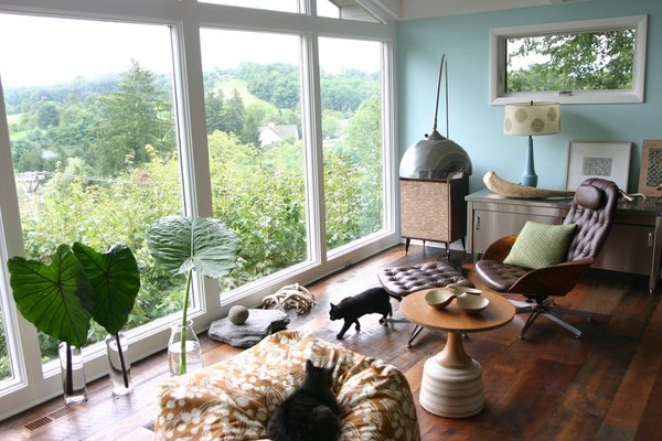 Textile designer Amy Butler lives in a post-and-beam midcentury house in Granville, Ohio, where she's paired her own fabrics and wallpaper with streamlined vintage pieces like a Mulhauser for Plycraft chair upholstered in brown leather. Photo via Dose of Happy.