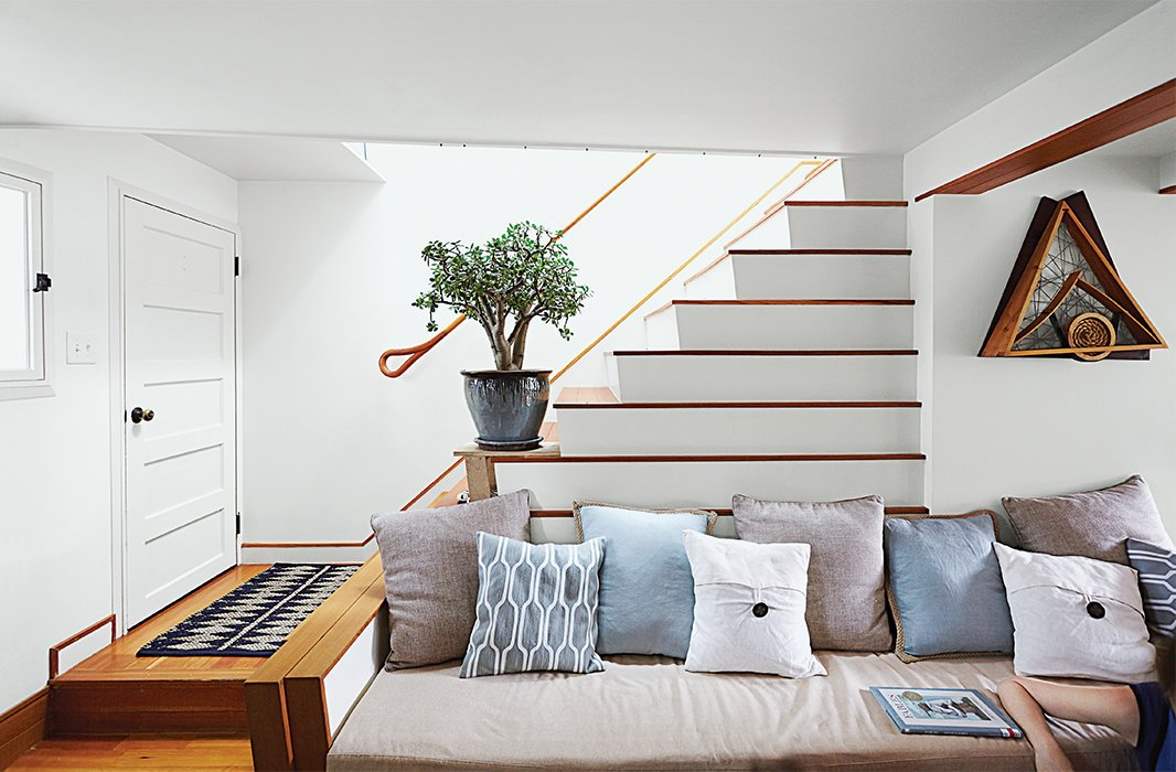 Living Room, Sofa, Medium Hardwood Floor, and Rug Floor In the living room, the stair's lower step reaches out to form an arm, while the ascending stairs create a natural incline for cushions.  190+ Best Modern Staircase Ideas from Run-Down Row House in Boston Becomes a Quiet Urban Escape with Two Green Roofs