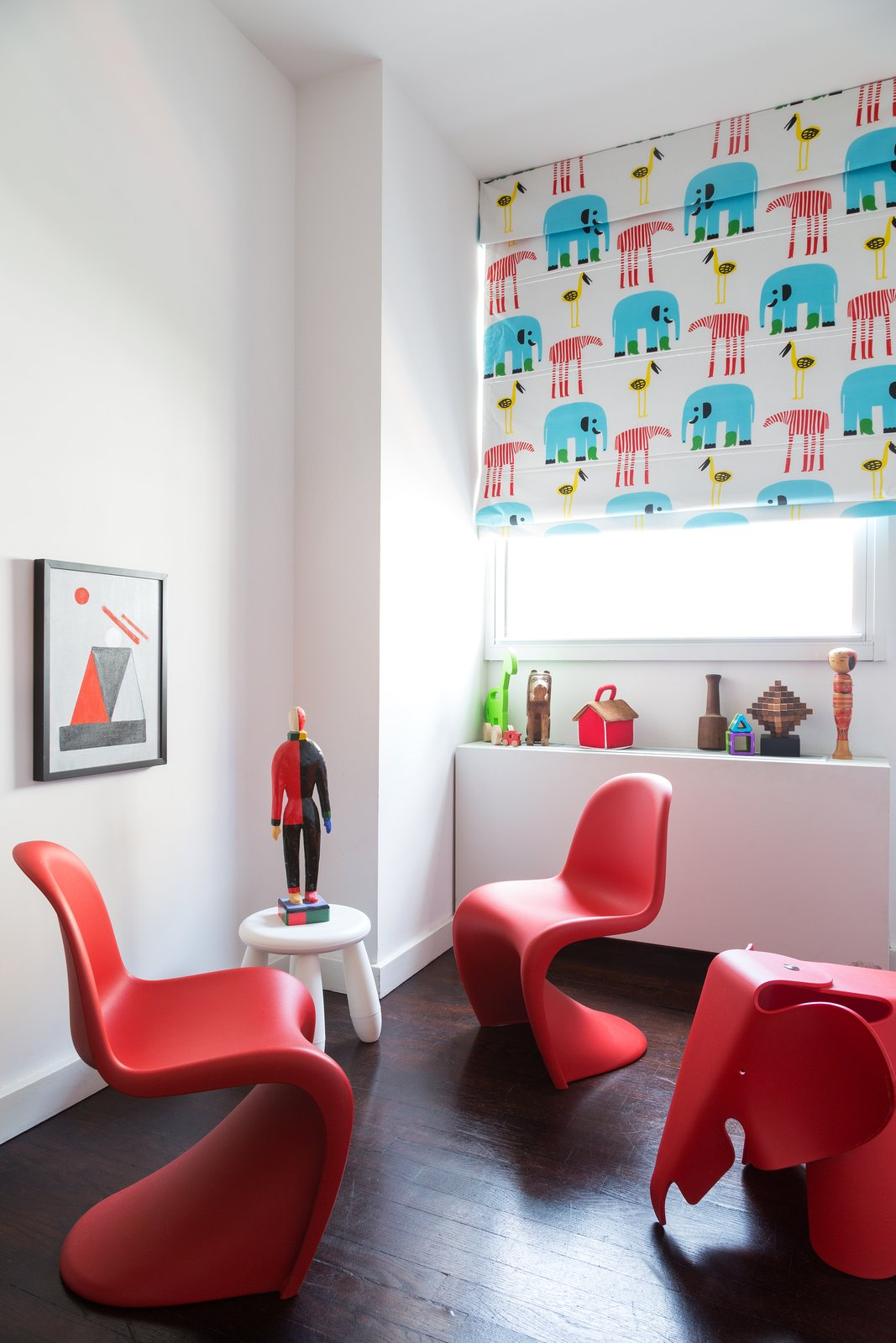 Kids Room, Playroom Room Type, Chair, and Dark Hardwood Floor Panton chairs from Vitra adorn the guest bedroom and office.  Lovely NYC Abodes That Will Give You Apartment Envy by Allie Weiss from Furnish by Color: Red