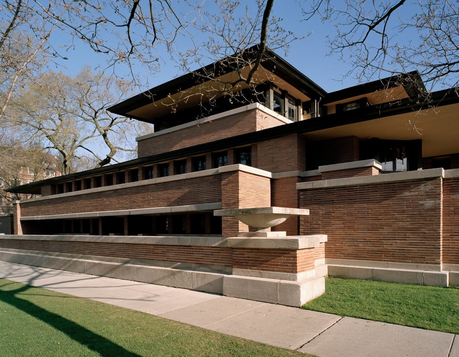 """Robie House, Chicago, Illinois (1910)""""Early in life I had to choose between honest arrogance and hypocritical humility. I chose honest arrogance."""" It should come as no surprise who uttered those words—the architect of the famed Robie House, Frank Lloyd Wright. The residence, with its tight recessed entry leading to dramatic light-filled openness, seamless space unencumbered by needless partitions, continuous bands of windows, its horizontal, low-slung form, and overhanging eaves, is what the architect called """"a cornerstone of American architecture.""""  Tiny Homes from Buildings That Changed America"""