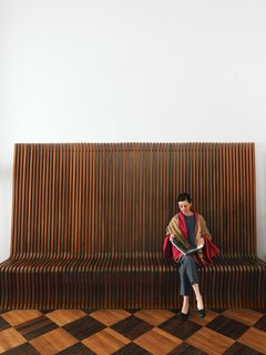 Here, Smith sits on a vintage rosewood bench designed by the Swiss-born British architect Richard Seifert.