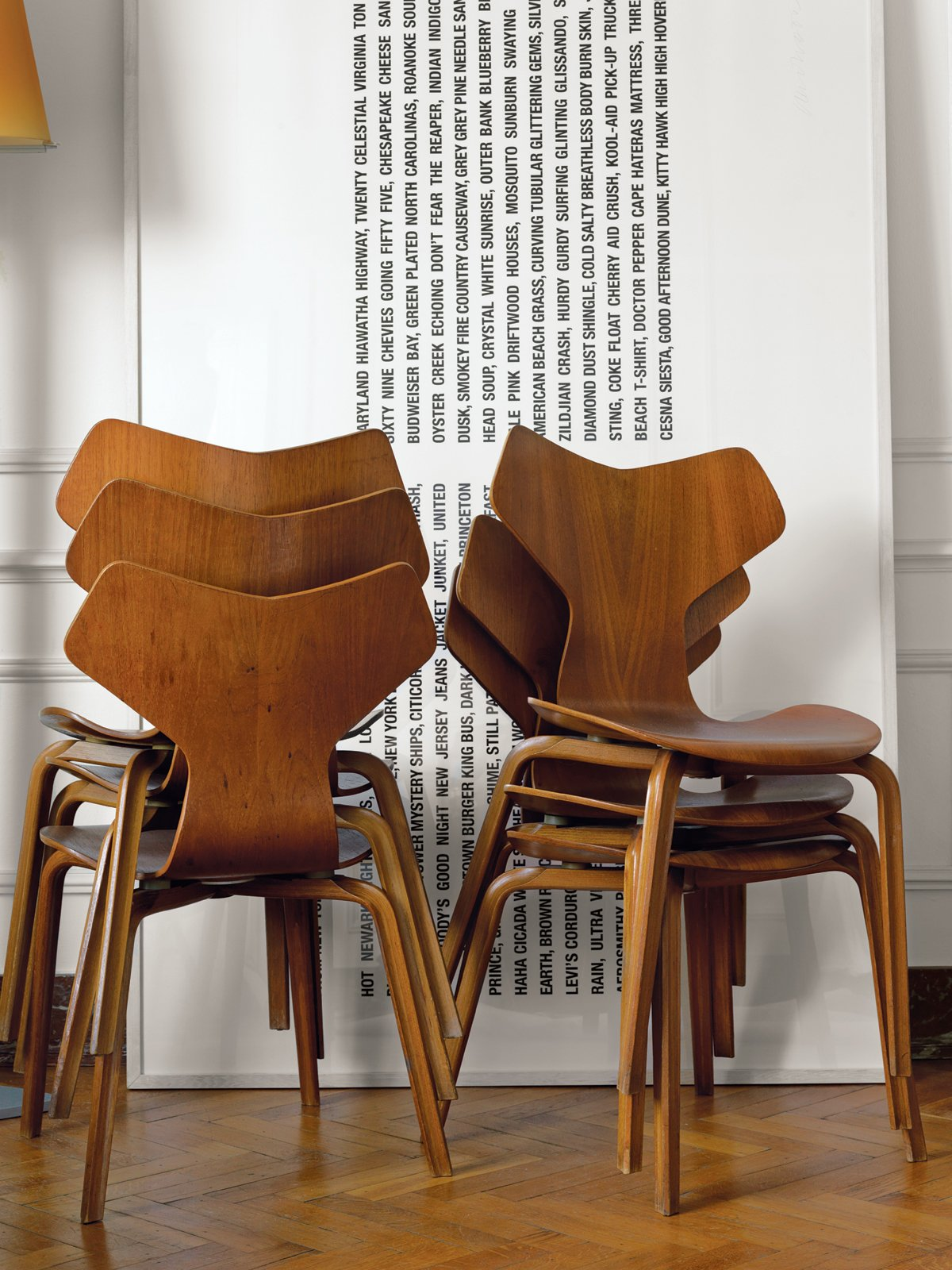 Living Room and Chair A stack of 1955 Grand Prix chairs by Arne Jacobsen rests besides a minimal art piece.  Ways to Decorate with Arne Jacobsen Furniture by Erika Heet from A Neoclassical Gallery Home in Belgium