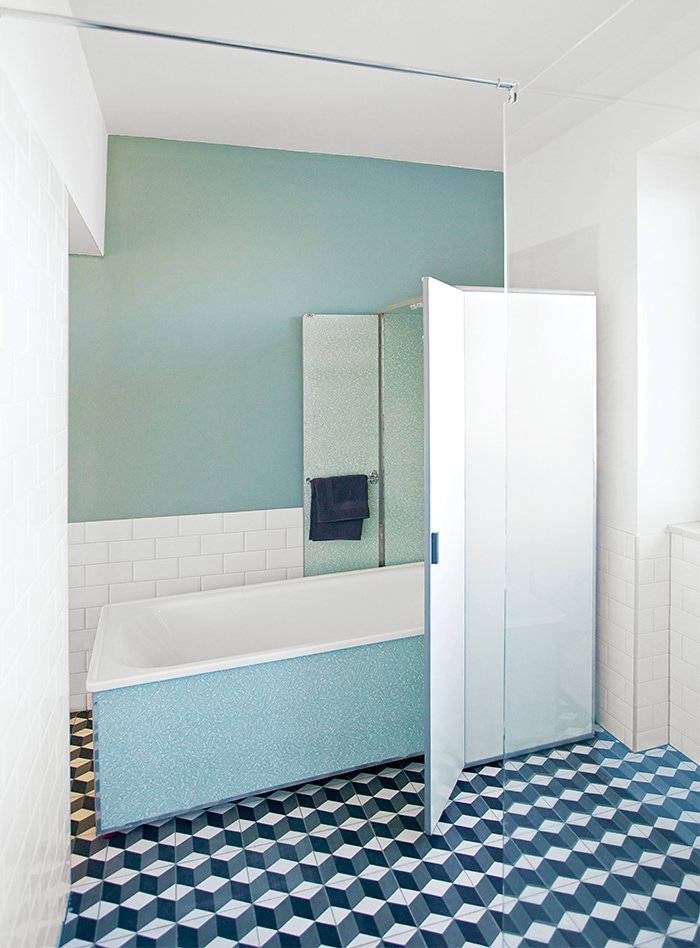 """For the bathroom, Reckendorfer wanted a shower for daily use, but opted to keep a 1950s bathtub that she discovered in her basement. """"I studied graphic design and photography, so visual things are so important to me,"""" she says. """"I love sleek, light-filled Scandinavian designs, but I also love flea markets and pieces with history.""""  Photo 8 of 11 in 10 Ideas For Designing With a Modern Bathtub from A Space-Saving Bathroom Renovation With an Amazing Fold-Up Tub"""