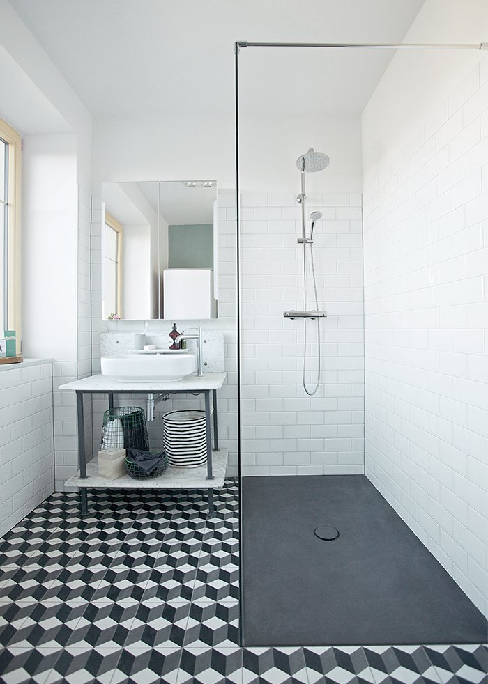 Bath Room, Vessel Sink, Subway Tile Wall, Cement Tile Floor, and Enclosed Shower In renovating her home in Schönkirchen-Reyersdorf, Austria, Katharina Reckendorfer repurposed what she could—like a bathtub and vanity—and streamlined the rest. New black and white graphic cement tile from Mosaic del Sur, Hansgrohe fixtures, a shower plate from Bette, and Farrow & Ball's Chappell Green paint round out the room.