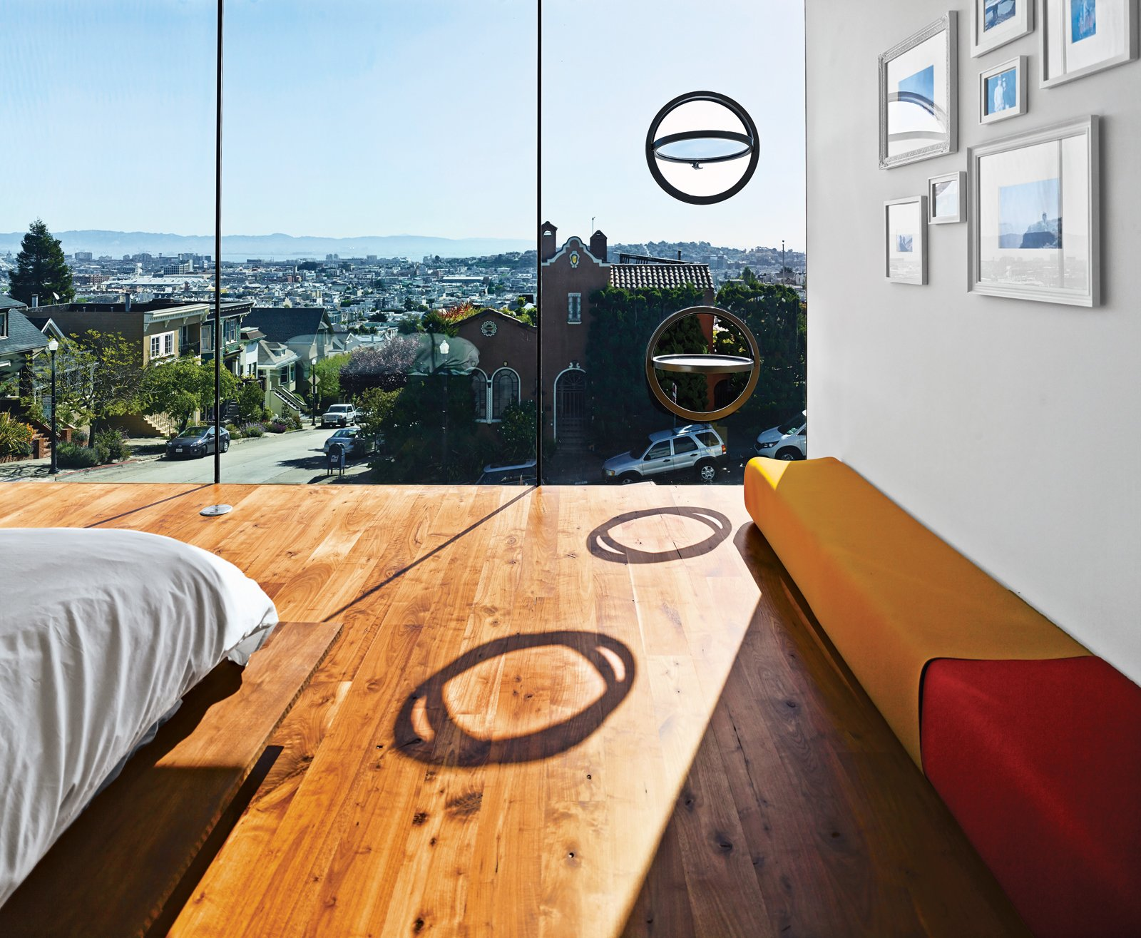 Bedroom, Bed, and Medium Hardwood Floor The LC4 lounge is by Le Corbusier, Charlotte Perriand, and Pierre Jeanneret for Cassina. Operable porthole windows on the east facade offer ventilation.  Photo 11 of 17 in Striking Slatted Wood and Glass Home in San Francisco