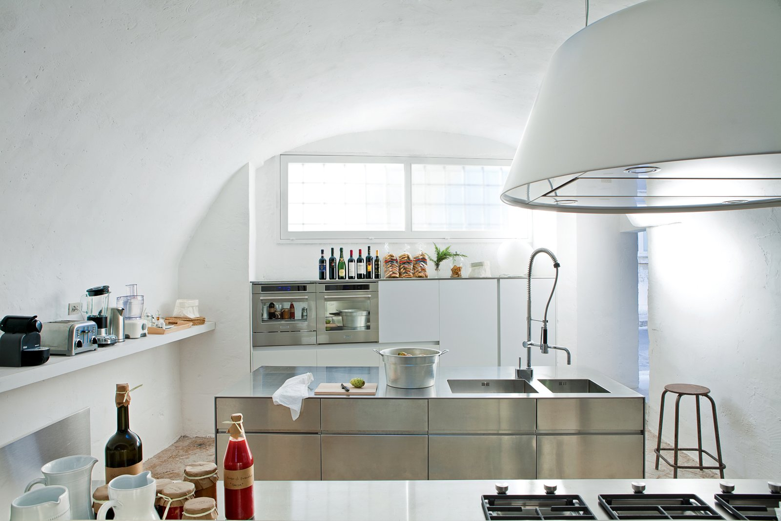 "Kitchen, Metal Counter, Metal Cabinet, Drop In Sink, Range Hood, Wall Oven, Table Lighting, Range, Microwave, Limestone Floor, and White Cabinet The acclaimed Italian designers Ludovica+Roberto Palomba carved a serene retreat out of a 17th-century oil mill in Salento, Italy, filling it with custom creations and their greatest hits. In their minimalist kitchen: sleek steel cabinet systems and the Kono range hood from Elmar. The multi-functional stainless steel island measures 20"" deep and was designed by the couple for Elmar.  Photo 7 of 8 in Modern Meets Ancient in a Renovated Italian Vacation Home"