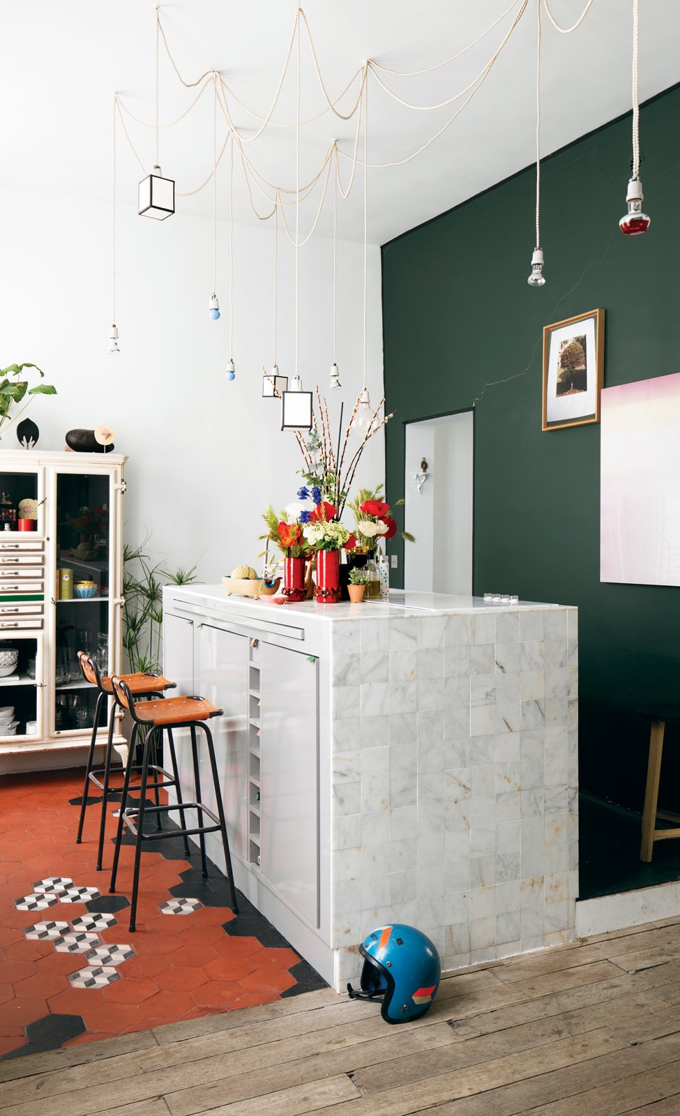 Kitchen and Marble Counter Aumas designed the kitchen island, which is covered in marble tiles from Carrelages du Marais—the geometric floor tiles are from the same place—and strung the matrix of lights up above it. The barstools by Charlotte Perriand were discovered in a vintage store in Antwerp, Belgium. The green wall is covered in paint from Emery & Cie.  Material Focus: Marble by Diana Budds from A Furniture Collector's Renovated Flat in Paris