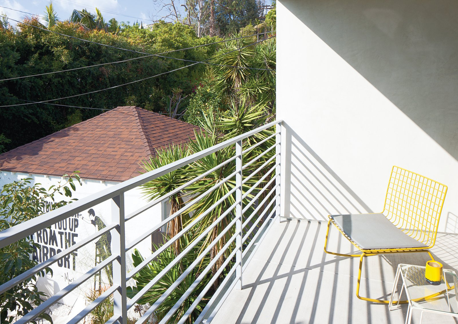 Outdoor, Concrete Patio, Porch, Deck, and Small Patio, Porch, Deck On the balcony off the master bedroom is a yellow Hatfield Grellow rocker from CB2.  Photo 3 of 13 in The Modern Renovated Home of Glee Star Jayma Mays