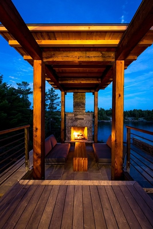 A covered fireplace and sitting area anchor the deck, which overlooks the water.  Monument Channel Cottage by Allie Weiss from Modern Meets Rugged at This Off-the-Grid Retreat in Ontario