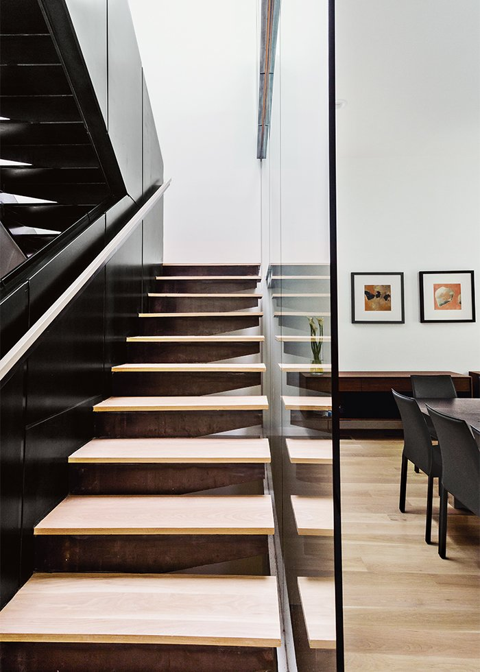 Staircase and Metal Railing The fireplace surround and staircase are fabricated from steel with a clear coat. Enclosed with glass on two sides, the space allows nature to flow inside.  Modern Glass-Encased Staircases by Brandi Andres from This Woodland Home in Virginia Was Built for Modern, Multigenerational Living
