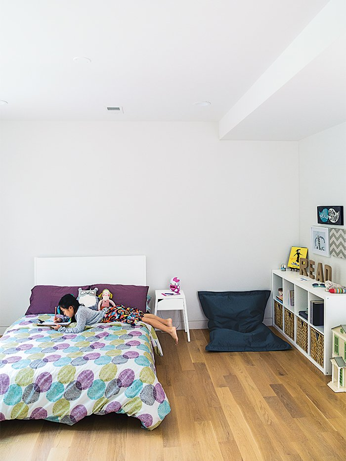 Bedroom, Bed, Shelves, Night Stands, and Storage The kids' bedrooms are located on the second story. Karis's room is furnished with a Fatboy beanbag chair.  Photo 7 of 11 in This Woodland Home in Virginia Was Built for Modern, Multigenerational Living