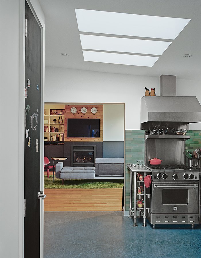 Kitchen, Range, and Range Hood The property is comprised of a succession of buildings that extend from the street-facing entrance. The 1,215-square-foot main house is the last of the three.  Photos from Abandoned Industrial Compound Becomes a Modern Home Base