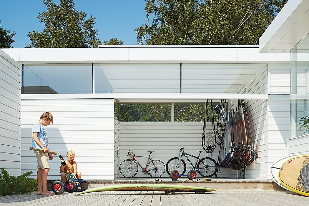 """Outdoor, Large Patio, Porch, Deck, and Wood Patio, Porch, Deck The family are avid fans of watersports of all stripes: """"Windsurfing and the stand-up paddling board—the beach is right outside,"""" says Henrik. """"It's a fun house.""""  Photo 3 of 10 in A Scandinavian Summer Home Built for Surf, Sports, and Sun"""