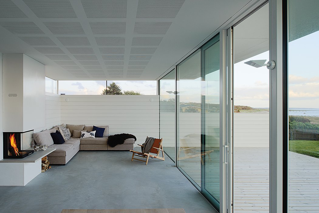 Living Room, Concrete Floor, Chair, Sofa, Wood Burning Fireplace, and Standard Layout Fireplace The living room features a sofa by Sits and a 1950 Hunting Chair by Børge Mogensen.  Photo 6 of 10 in A Scandinavian Summer Home Built for Surf, Sports, and Sun