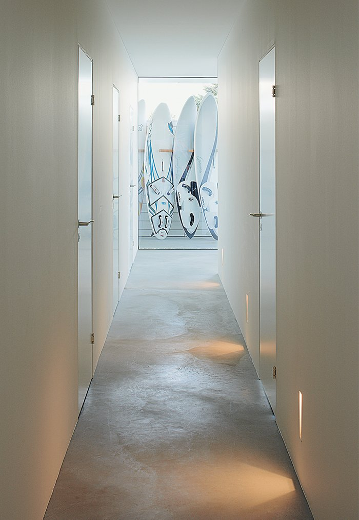 """Hallway and Concrete Floor """"The floor is one of my favorite parts of the house, as it was a real challenge for the construction—we only had one chance."""" —Henrik Lepasoon, resident  Photo 7 of 10 in A Scandinavian Summer Home Built for Surf, Sports, and Sun"""