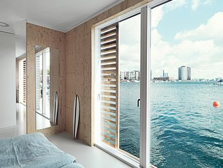 Glass doors grant the bedroom an immediate connection to the water.