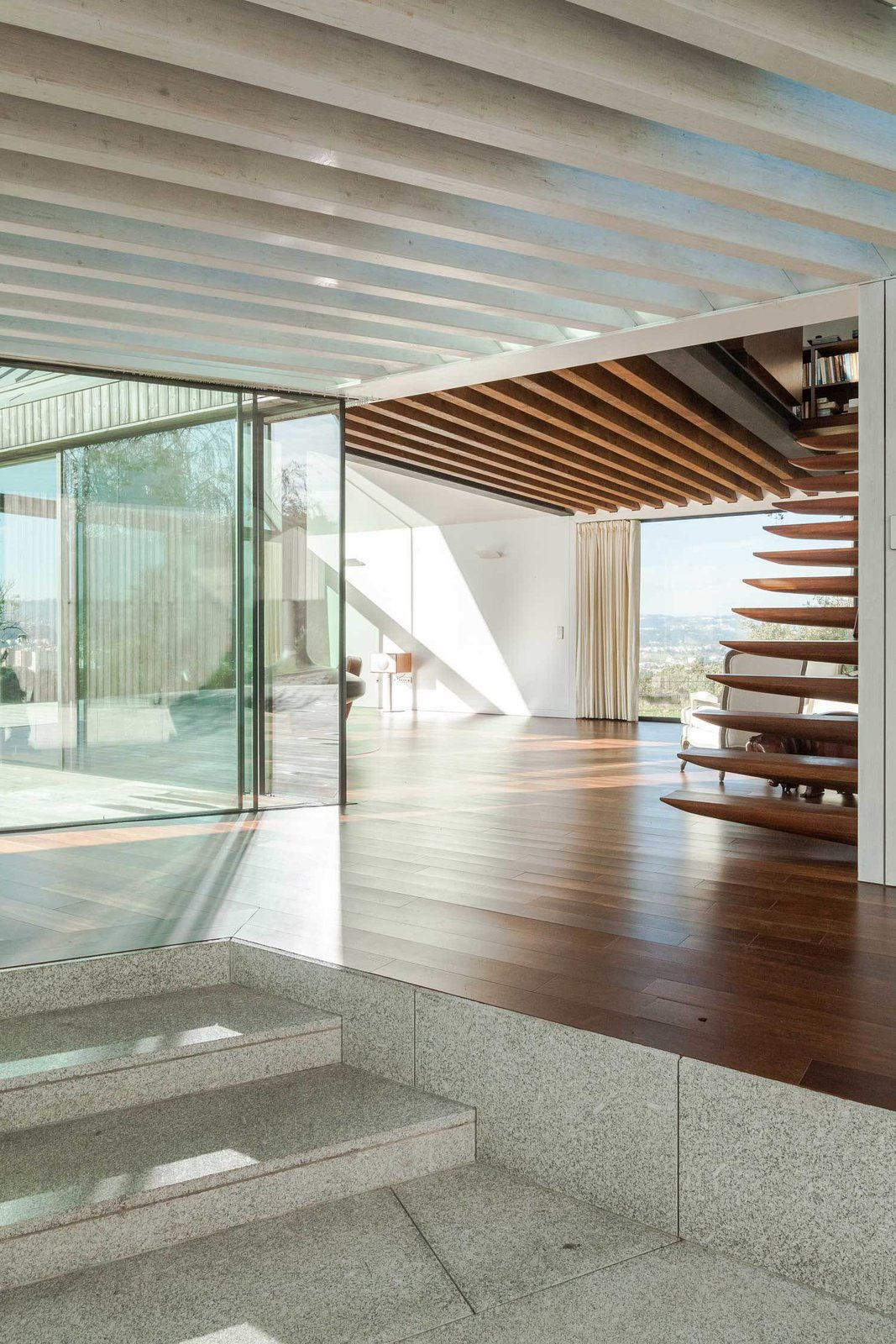 """The connecting area between the four houses has an open joisted pine ceiling that offers a masterful transition between the coarse, weathered exterior and the polished rooms—all lined with smooth Sucupira wood and white plaster board. """"We wanted to make a clear contrast between the interior surfaces of the house and the corresponding exterior surfaces,"""" de Carvalho says. Tagged: Staircase and Wood Tread.  House of Four Houses by Laura C. Mallonee"""