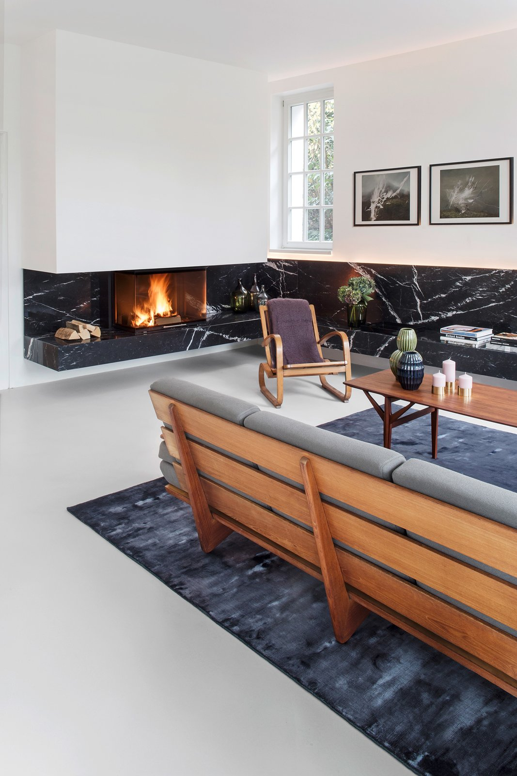 Nero Marquina marble is used in multiple rooms. In the living room, a strip of stone defines a bench that wraps around the space. Both the sofa and armchair are vintage.  Ways to Define Spaces With Area Rugs by Heather Corcoran from Black Marble Runs Through This Refined Berlin Apartment