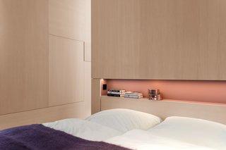 An elegant built-in shelf lies above the bed.
