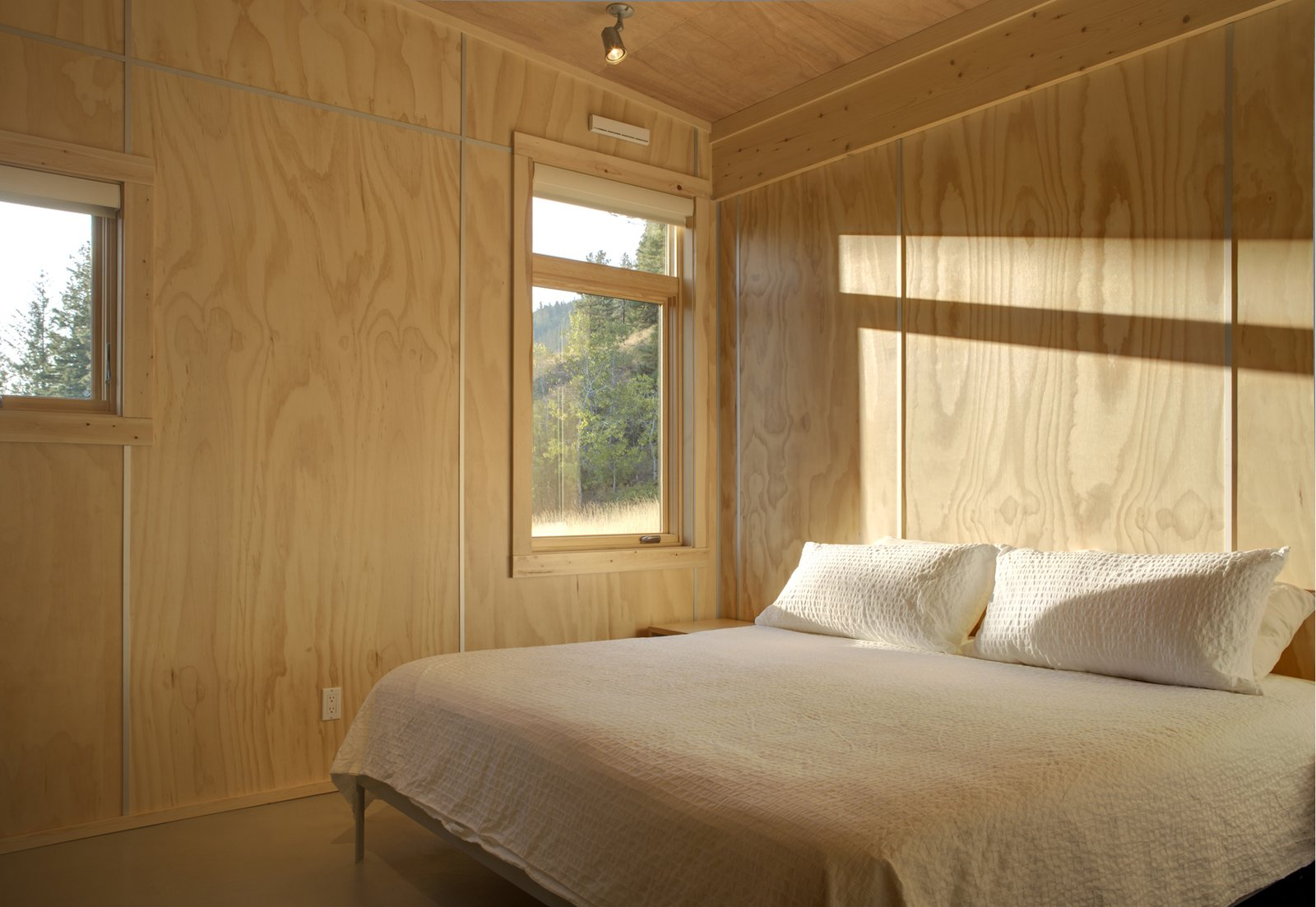 The bedroom is to the immediate right of the entrance; the architects selected plywood for interior surfacing for the warm tones it provided. The aluminum spacers allow for easy installation—they have greater tolerances for gaps as compared to other joints—while doubling as a decorative element.  Our Favorite Bedrooms
