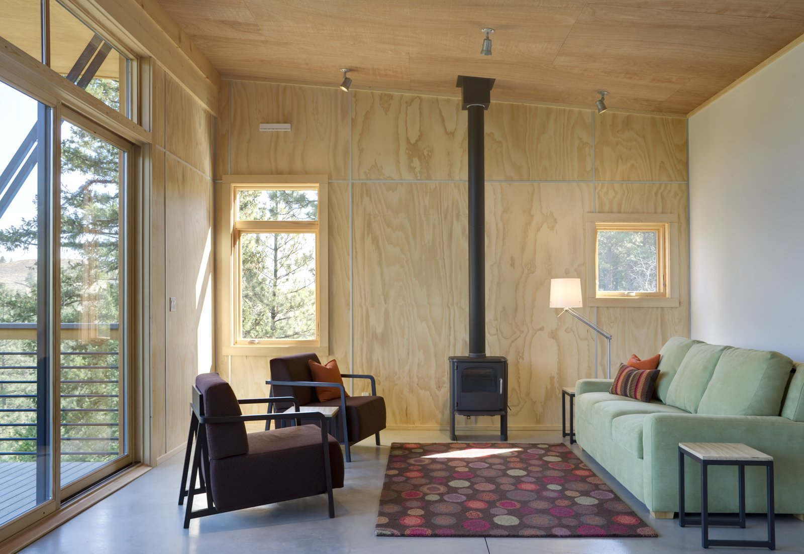 While the home is well insulated on all sides, the hearth can provide extra warmth when necessary.  Simple Cabin Embraces Its Mountain Setting by Zachary Edelson