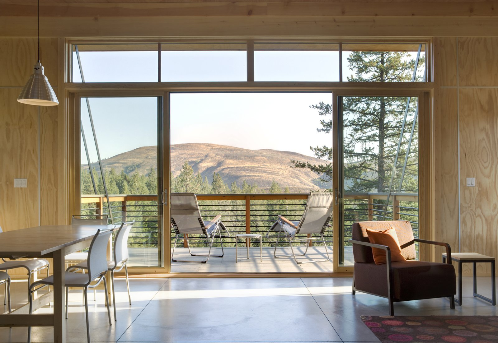 Supported by steel strips, the balcony extends outwards to meet the valley below. Fully-glazed sliding doors and a clerestory window provide a view.  Simple Cabin Embraces Its Mountain Setting by Zachary Edelson
