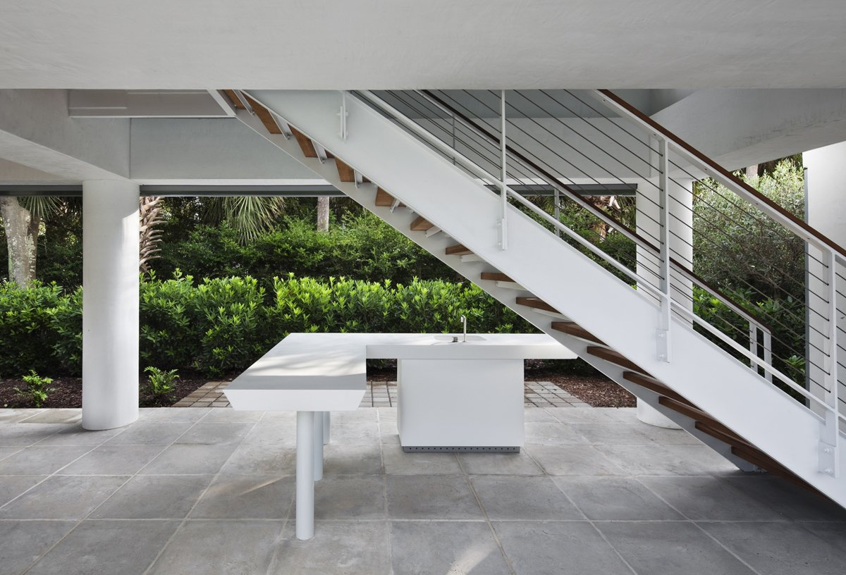 Outdoor, Concrete Patio, Porch, Deck, and Shrubs Underneath the raised pavilion, the architect carved out an updated version of the classic Southern veranda. This one sports a minimalist outdoor kitchen and all-white accents with a cypress ceiling.  Photo 3 of 6 in Summer-Ready Modern Pavilion in South Carolina
