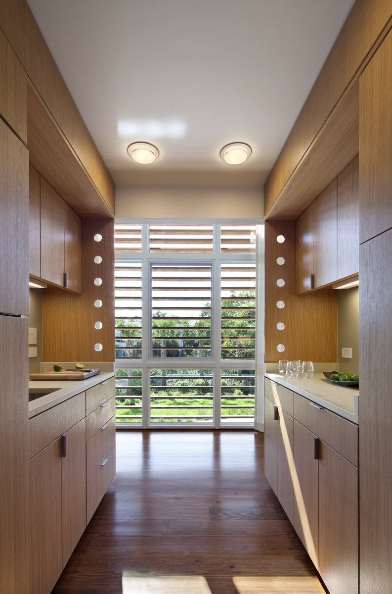 """Kitchen, Wood Counter, and Light Hardwood Floor A sleek galley kitchen packs function and style into a small space.  Search """"7 small spaces incredible kitchens"""" from Summer-Ready Modern Pavilion in South Carolina"""
