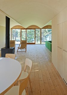The first floor contains communal rooms (kitchen, living room, etc.) and private sleeping spaces are located above. The dining room table and chairs are from Artek.