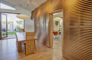 Garten's husband, sculptor Cliff Reid, envisioned the vibrant wood wall separating the living room and kitchen.