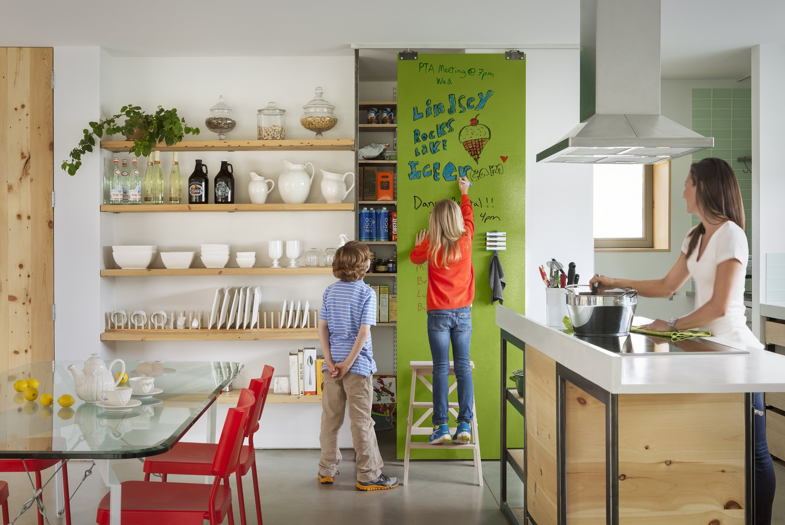 Kitchen, Open Cabinet, Range Hood, Cooktops, Wood Cabinet, and Concrete Floor An IdeaPaint wall in full effect in a family's kitchen. The company, which is exhibiting at Dwell on Design (booth #1009), is recruiting their onsite artist, Derek Cascio, to create a special wall for kids to color and scribble on in the Modern Family Pavilion (booth #901) Saturday and Sunday, May 30 and 31.  Photo 3 of 8 in 7 Ways to Child-Proof Your Home Without Forgoing Style from Your Guide to Dwell on Design 2015 Is Here