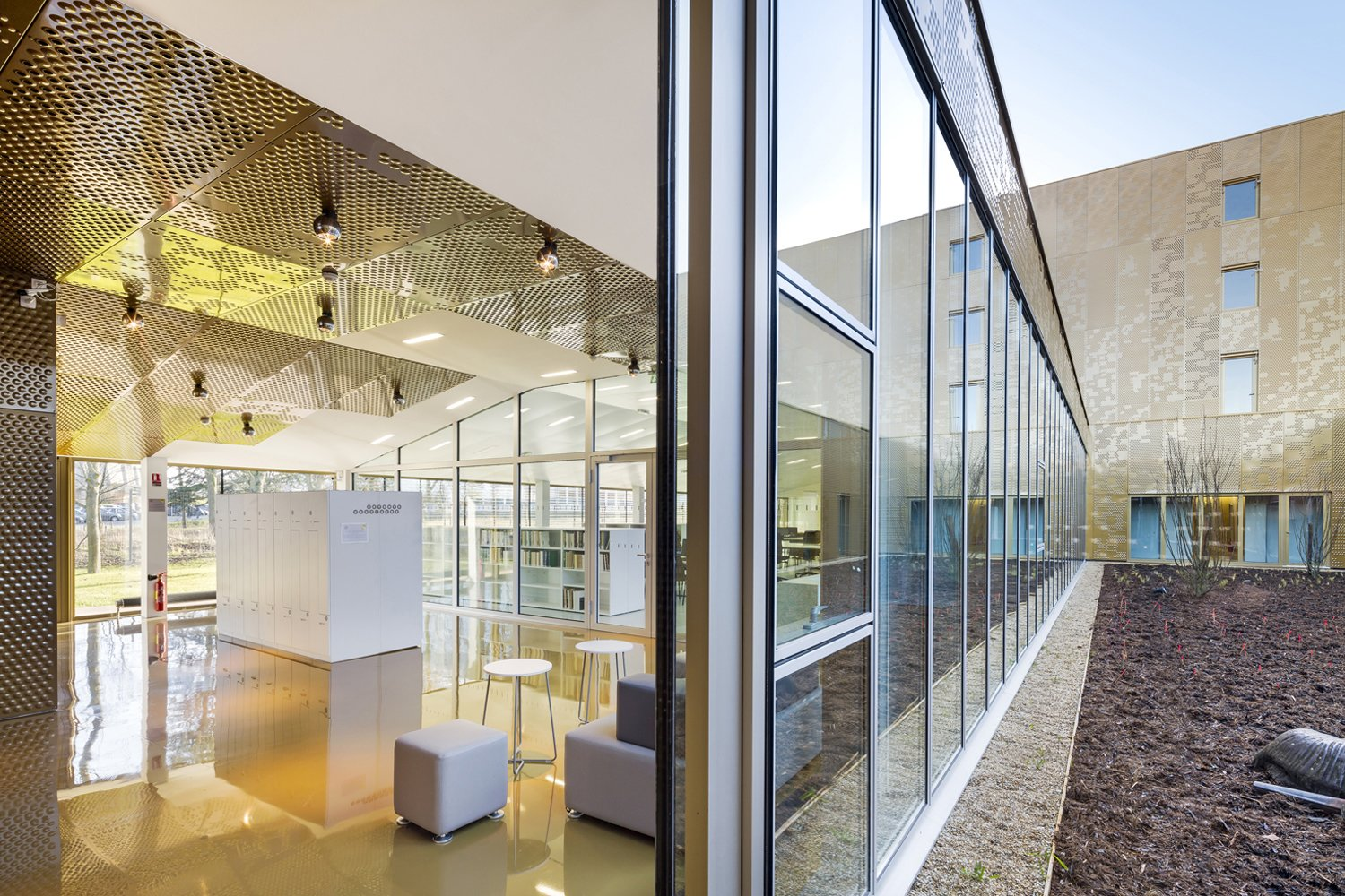 """The metallic motif continues indoors. Large expanses of glass let light in, which plays against the reflective ceiling, walls, and floors.  Search """"fences,-walls--metal"""" from French Archives Building Wrapped in a Dazzling Gold Shell"""