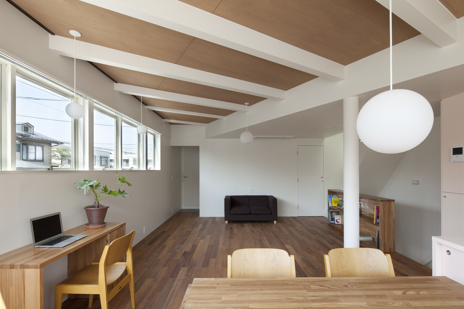 The ceilings of the two houses were at slightly different heights, an incongruity Nakasi played up for visual punch. He exposed the beams in the higher ceiling and painted them white to match the smooth finish of the lower one. The desk beneath the window is from Muji.  Modern Homes in Tokyo by William Harrison