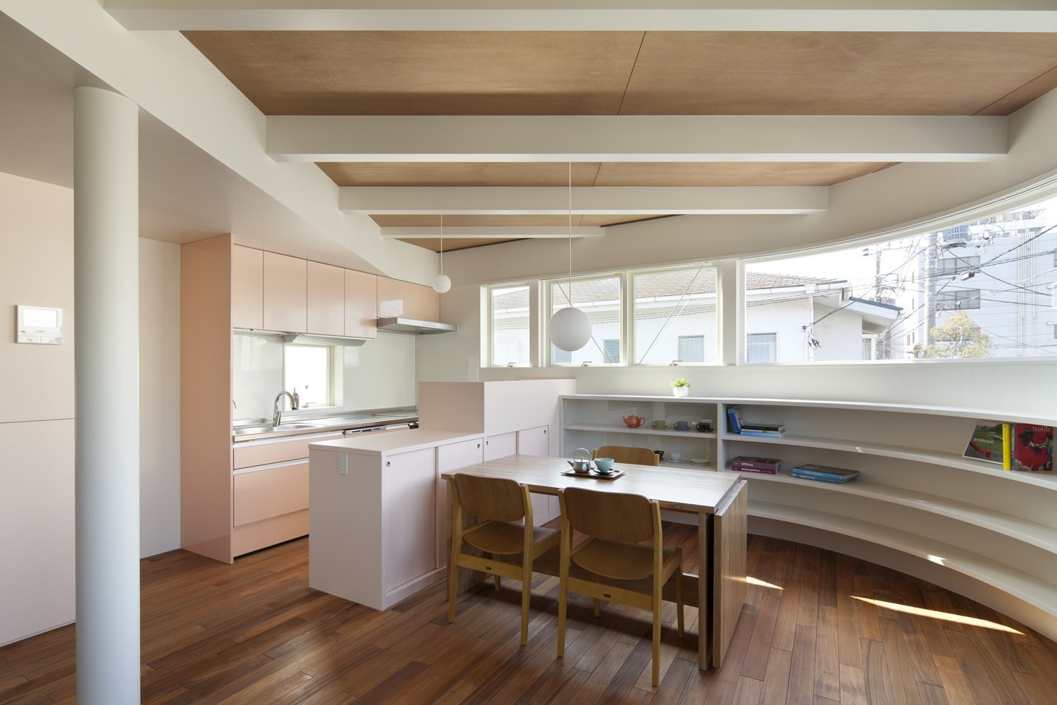 The kitchen and dining area features an integrated system by LIXEL, a custom-made table, and Tendo chairs. A bespoke, curved bookshelf wraps around the wall beneath a panoramic window.  Half & Half House by Laura C. Mallonee