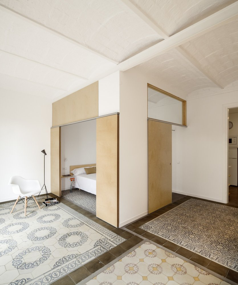 This renovated apartment in Barcelona plays with subtle color contrasts, such as the chromatic tile mosaics and the blond wood used for sliding doors and benches.  Photo 1 of 8 in 1930s Barcelona Apartment Gets a Minimal Makeover