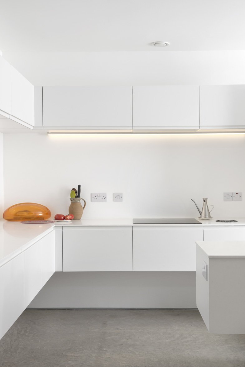 The stark white minimalist kitchen features quartz countertops, a Gessi Oxygene tap, a 1810 Company Zenuno sink, and energy-efficient Bosch appliances.  Minimal Kitchens by Allie Weiss