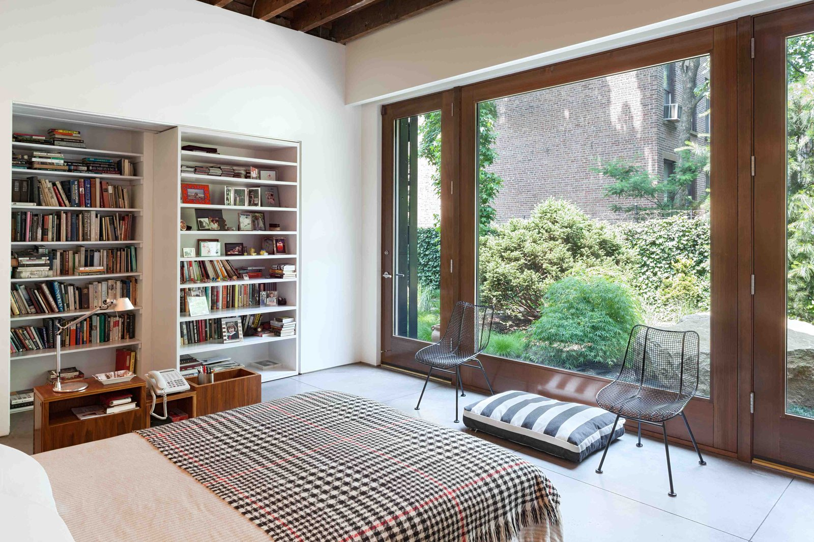 The bedroom can be closed off from the painting studio with a heavy sliding bookshelf on rollers.  Photo 2 of 8 in This Spacious Home in a Former Warehouse is Part Art Gallery