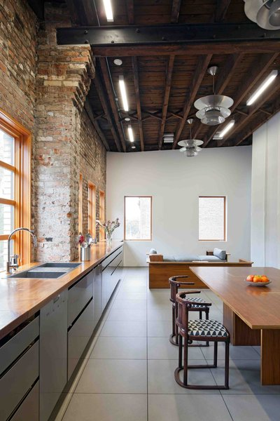 What the original building lacked in period detailing, it made up for with massive interior spaces, natural light, and a hardy palette of wood and raw brick.  Working with these loft signatures, David developed the hall's liveable side, adding under-floor heating, and a gigantic kitchen on the upper floor running the width of the building, with a 37-foot-long solid walnut counter on top of stainless steel cabinets. This unites the dining, cooking and social spaces that run the length of the front façade on the upper floor.
