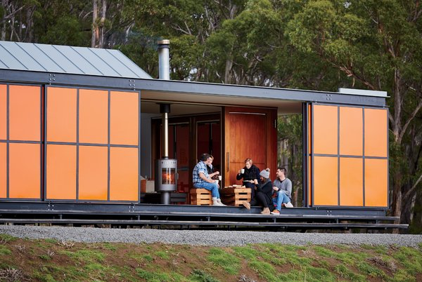 """The Premaydena House by Misho+Associates was designed as a """"box within a box,"""" in which two interior structures—an open-plan living space and two en suite bedrooms—sit within an exterior envelope. Inspired by the region's fiery orange lichen and the indigenous waratah shrub's bright flowers, the colorful exterior panels are made of heavy-duty galvanized steel to guard from Tasmanian winds, which can reach up to 60 miles per hour."""