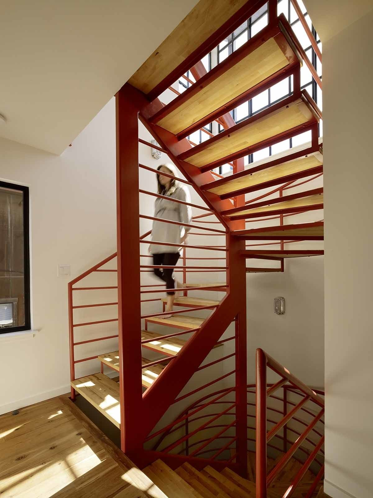 "Staircase, Metal Railing, and Wood Tread Fabricated by Stocklin Iron Works and designed by Nebolon, the orange staircase features steel railings and treads made from IKEA wood butcher blocks. ""We designed the open staircase to make the trip to the second floor fun,"" the architect says.  Best Photos from Like a Loft on Water"