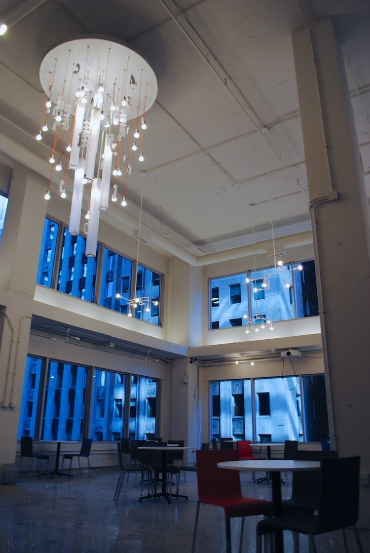 "Grind (Chicago, United States)  This Chicago workspace shed the drop ceilings and depressing decorations of its former life as a title insurance company to blossom into a coworking hotspot. Benjamin Dyett, co-founder of Grind, which also runs similar spaces in New York, says his team wanted to create a ""frictionless workspace"" and built an array of desks and conference rooms to accommodate different work styles, all buffered by a sound attenuation system that improves focus. A 22-foot-high ceiling, massive windows and an internal mezzanine provide an airy, open environment, while custom light fixtures from Brooklyn's MESH Architecture and a chandelier/art installation by RND, made of old phone receivers and staplers recovered from the office's previous incarnation, provide visual inspiration when minds wander.  Photo 2 of 13 in 13 Inspiring Coworking Spaces"