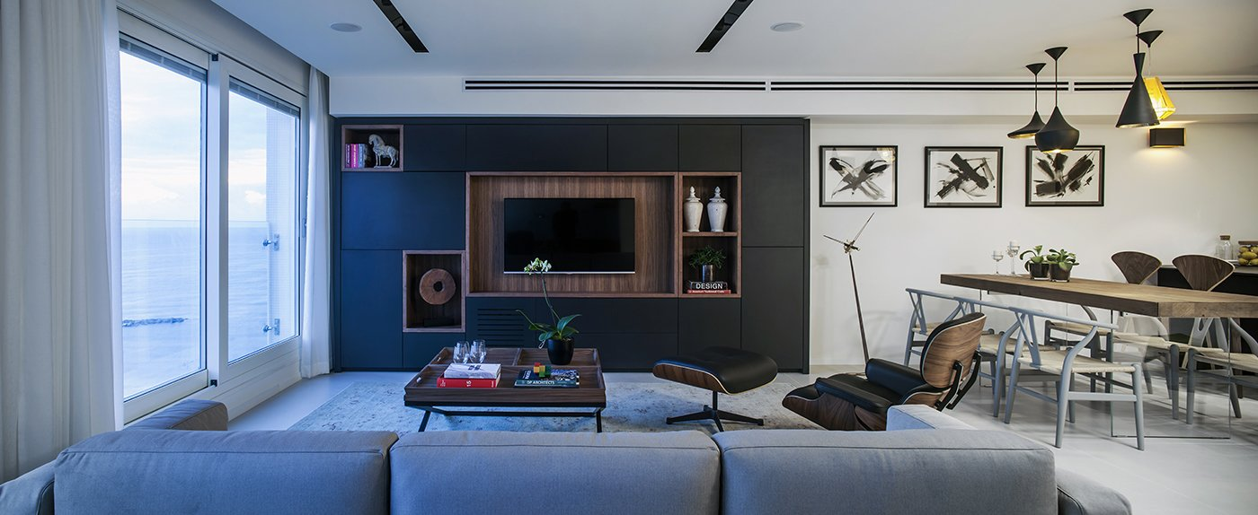 Architect and designer Roy David was tasked with renovating a 1,184-square-foot apartment located in a luxury tower in Tel Aviv. The remodeled living room features a Gus* Modern sofa and an Eames lounge chair.  A Compact, Renovated Apartment in a Tel Aviv Tower by Allie Weiss