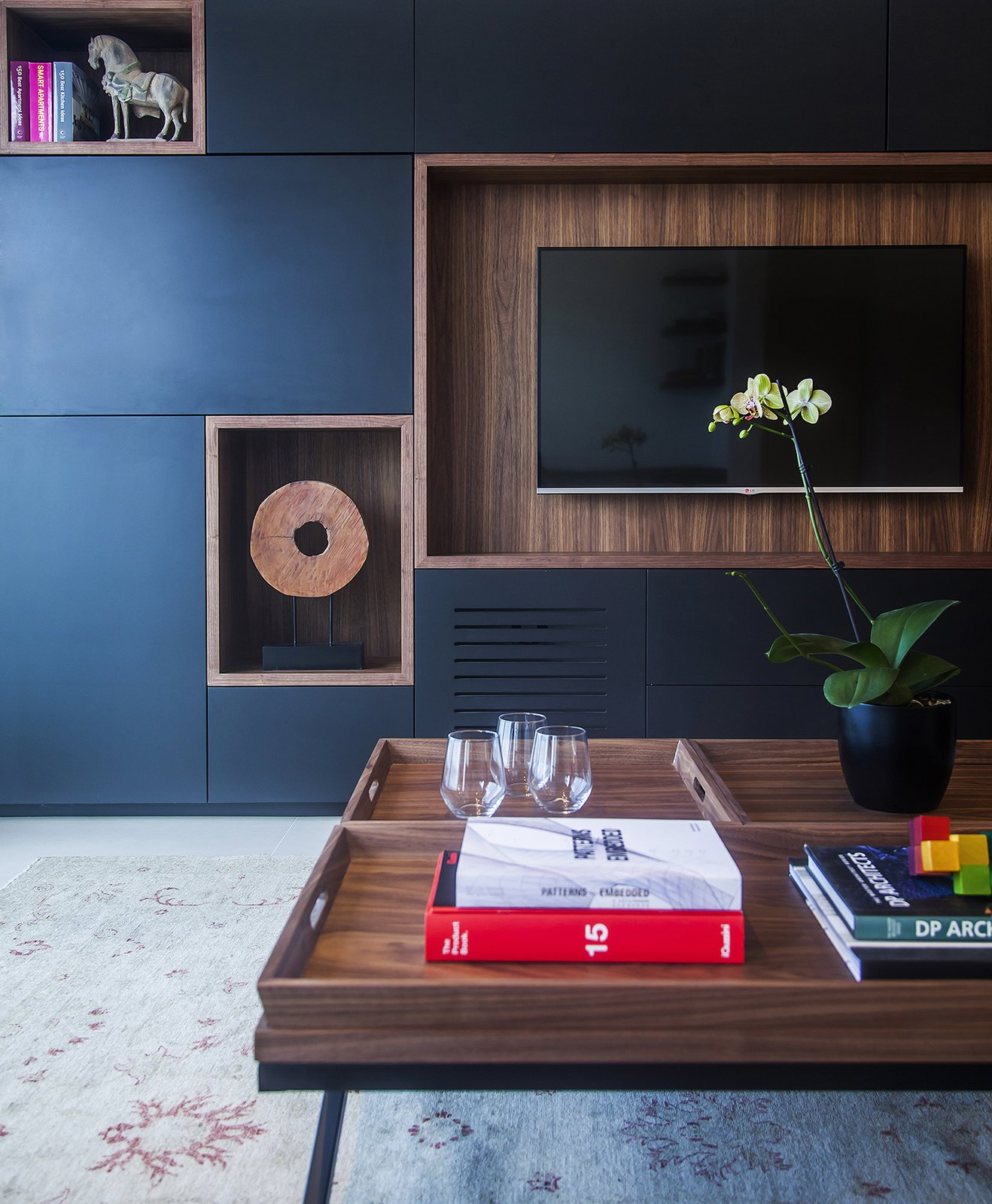 A custom media unit with hickory detailing features built-in shelves for displaying objects.  A Compact, Renovated Apartment in a Tel Aviv Tower by Allie Weiss