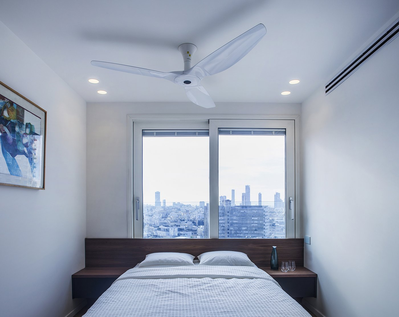 As part of the update, the two bedrooms were expanded, and a number of smart features were added: automated lighting and curtains, along with double glazed windows with an electric shading system.  Bedroom from A Compact, Renovated Apartment in a Tel Aviv Tower