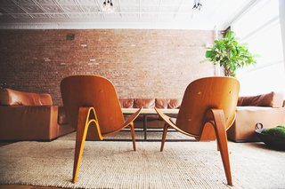 """Mixing mid-century modern with the iconic brick of downtown Manhattan is a sure fire way to live """"bachelor-chic"""". Photo by Chellise Michael Photography."""
