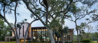 """The house is set in a privately owned nature preserve halfway between Charleston and Savannah, on an isthmus between a marsh and a pond. """"It's a cool site, very exotic,"""" says architect James Choate. """"It feels like a wildlife sanctuary."""" The resident, a man who works in commercial real estate, wanted a big space with glass walls to """"honor the views."""""""