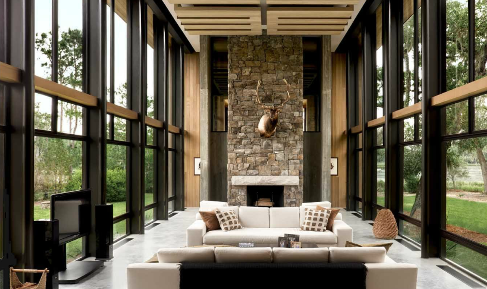 The grand, glass-walled great room is a loft-like space that incorporates living room and dining area. A bedroom and bathroom are located on a lofted mezzanine level, over the kitchen, pantry, and utility room.  97+ Modern Fireplace Ideas from A Modern Home in a South Carolina Marsh