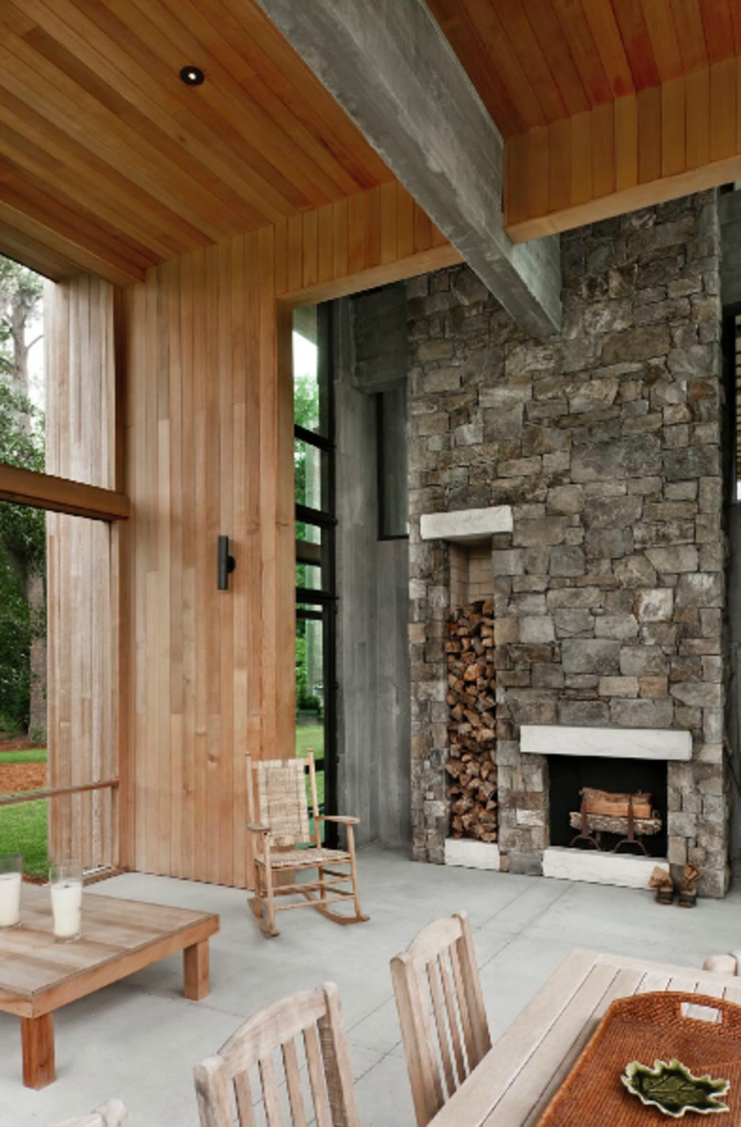 Choate selected maintenance-free materials for the project wherever possible, including the stone on this fireplace, which includes built-in storage for firewood. The stone extends 25 feet up to the wood-clad ceiling, emphasizing the home's grand scale.  97+ Modern Fireplace Ideas from A Modern Home in a South Carolina Marsh